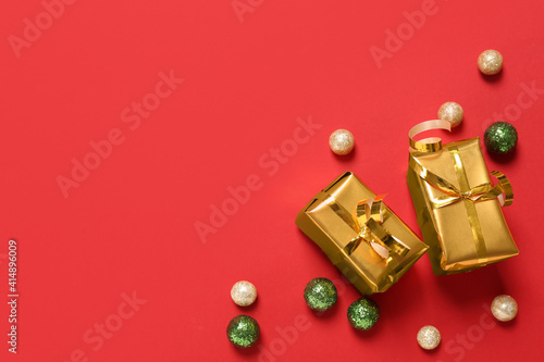 Fototapeta Gift boxes and Christmas balls on red background, flat lay. Space for text obraz