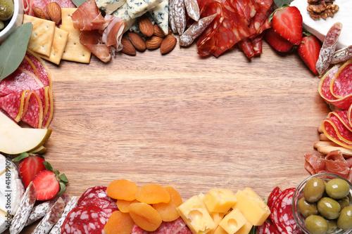 Fényképezés Frame of assorted appetizers on wooden background, flat lay