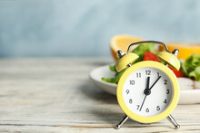Alarm Clock And Healthy Food On White Wooden Table, Space For Text. Meal Timing Concept