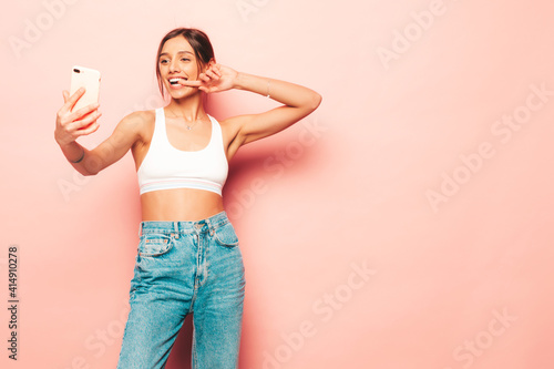 Obraz Beautiful smiling woman dressed in white jersey top shirt and jeans. Sexy carefree cheerful model having fun indoors.Adorable and positive female posing near pink wall in studio. Taking selfie - fototapety do salonu