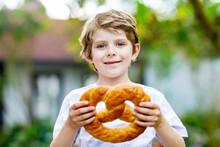Adorable Little Kid Boy Eating Huge Big Bavarian German Pretzel. Happy Blond Child Enjoying Tasteful Tratditional Bread. Healthy Food For Happy Kids.