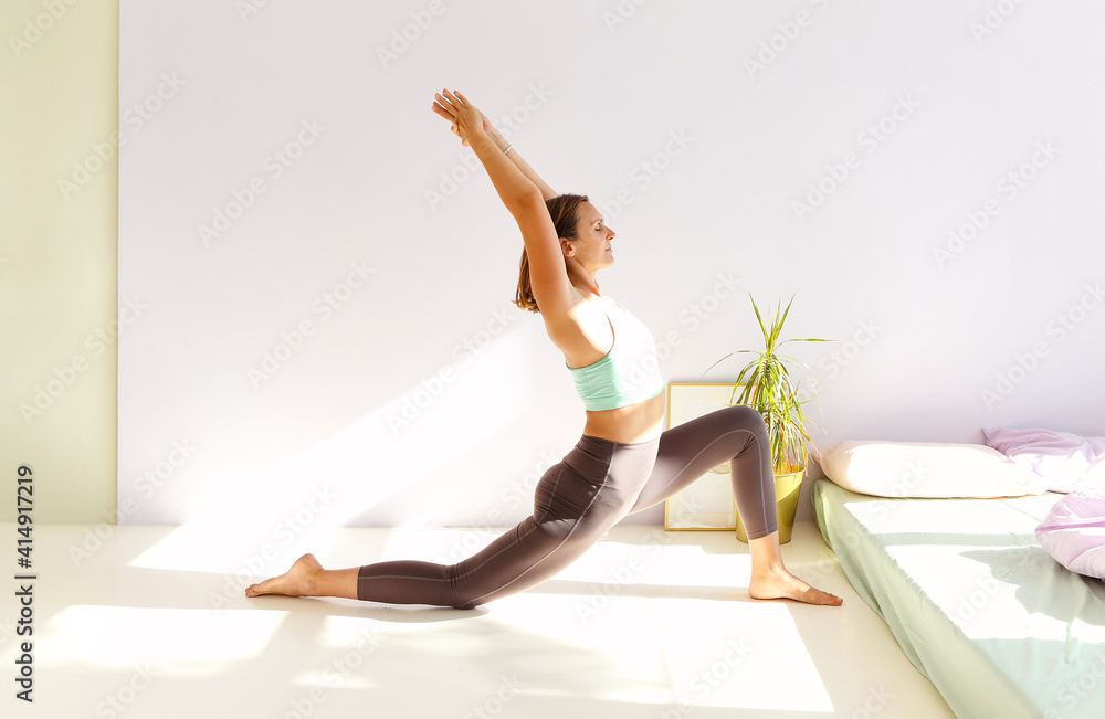 Fototapeta Flexible woman doing yoga at home