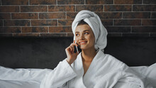 Happy Woman In White Towel And Bathrobe Talking On Smartphone In Hotel Room