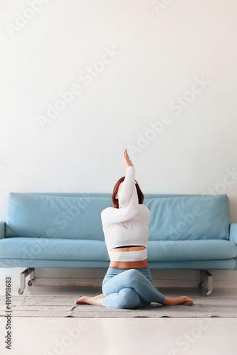Obraz Middle age woman having yoga session at home - fototapety do salonu