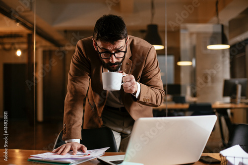 Young businessman working on laptop and drinking coffee in his office. Businessman on coffee break.