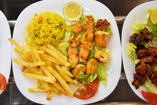 Chich Taouk With Rice And French Fries And Salad And Lemon