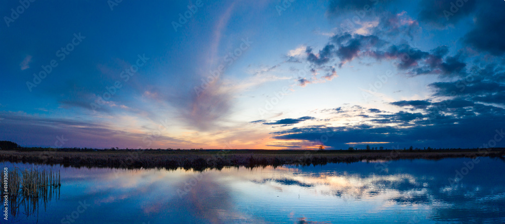 Fototapeta Beautiful sunrise and dramatic clouds on the sky. Flood waters of river. Panorama landscape