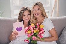 Photo Of Happy Mother And Daughter Sit Sofa Hold Tulips Heart Card 8-march Indoors Inside House Home