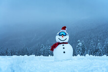 Funny Snowman In Ski Glass In Snowy Mountains. Ski Resort Concept. Merry Christmass And Happy New Year