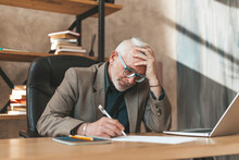 A Mature Man Is Desperate To Sign Debt Documents In The Office At The Table. Old Man Lost His Job, Stress And Bankruptcy.
