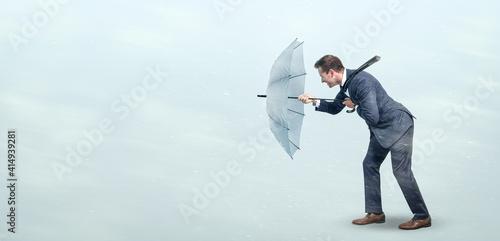 Fotografia, Obraz Businessman defying strong headwind