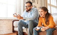 Father And Daughter Laugh And Play Video Games Together Using A Video Game Console
