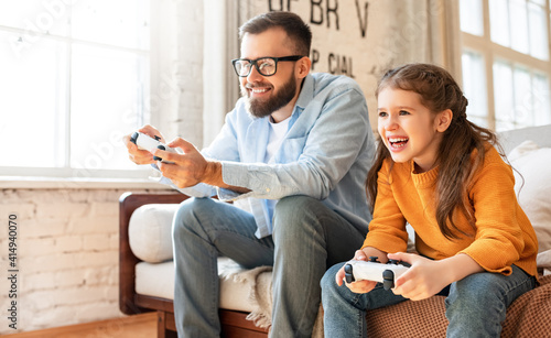 father and daughter laugh and play video games together using a video game console #414940070