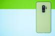 Light green mobile phone put vertically in the background of blue and green colors