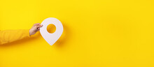 3D Location Symbol In Hand Over Yellow Background, Panoramic Image