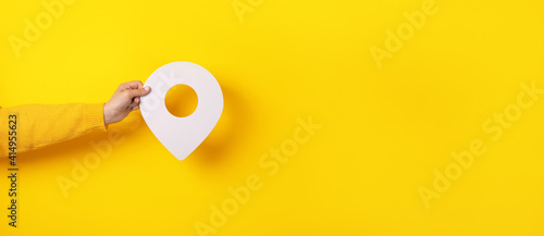 Photo 3D location symbol in hand over yellow background, panoramic image