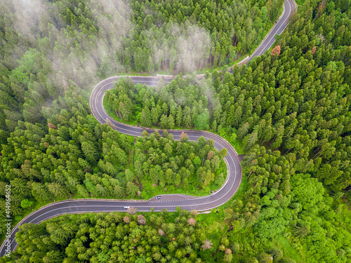 Obraz Winding road through the forest, from high mountain pass, in summer time. Aerial view by drone. Romania - fototapety do salonu