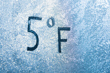 5 Degrees Fahrenheit Or -15 Celsius Number Lettering On Icy Glass Covered With Ice And Frost. The Concept Of Extreme Cold Weather
