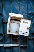 White Iron Old Rusty Mailbox With Open Door Hanging On Iron Grate