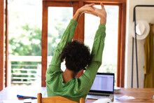 Rear View Of Caucasian Woman Sitting At Table Using Laptop Computer Stretching Arms In The Air