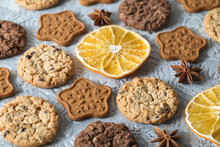 Oatmeal, Ginger And Chocolate Cookies, Slices Of Dried Oranges, Stars Of Anise On A Textured Gray Background
