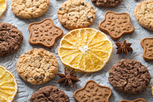 Oatmeal, Ginger And Chocolate Cookies, Slices Of Dried Oranges, Stars Of Anise On A Textured Gray Background. Side View
