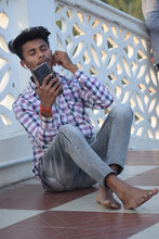 Portrait Of A Male Listening To Music On His Mobile Phone While Sitting On An Outdo