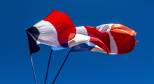 Closeup Low Angle Shot Of Waving Flags Of France On Poles Under A Clear Blue Sky