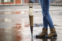 Woman With Umbrella Standing On City Street During Rain