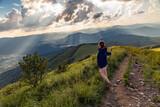 Turystka podziwia promienie światła oświetlające dolinę, w której znajduje się górska wieś Wetlina, Bieszczady, Polska