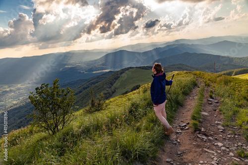 Obraz Turystka podziwia promienie światła oświetlające dolinę, w której znajduje się górska wieś Wetlina, Bieszczady, Polska - fototapety do salonu