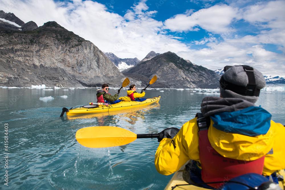 Fototapeta Group of friends enjoy ocean kayaking bear glacier during their vacation trip to in Alaska, USA