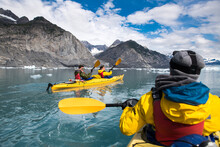 Group Of Friends Enjoy Ocean Kayaking Bear Glacier During Their Vacation Trip To In Alaska, USA