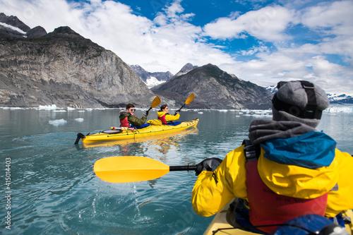Fototapeta Group of friends enjoy ocean kayaking bear glacier during their vacation trip to in Alaska, USA obraz