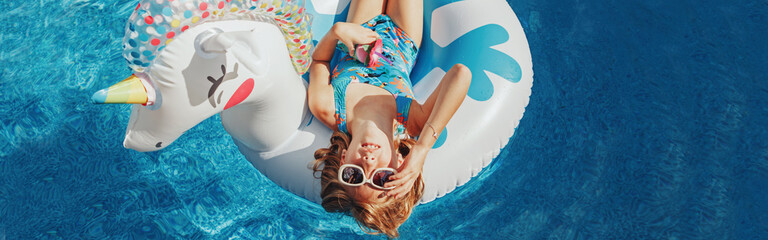 Cute adorable girl in sunglasses with drink lying on inflatable ring unicorn. Kid child enjoying having fun in swimming pool. Summer outdoors water activity for kids. Web banner header.