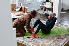 Senior Woman Doing Sit-up Exercises With Husband, Active Lifestyle Fitness