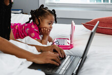 Toddler On Toy Laptop Next To Mother Who Is Working From Home