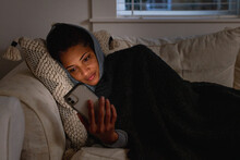 Black Woman Cozy On Sofa Checking Cellphone