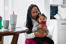 Toddler Watches Television Show On Phone Sitting In Mother's Lap