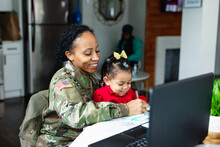 Military Mom And Daughter At Home Working