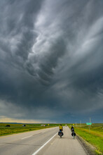 Cyclists On Road Under A Stormy Sky, Ontario, Canada