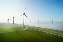 Offshore Wind Turbines Standing In Fog On The IJsselmeer Inland Sea, Land Based Turbines In The Clear, Flevoland, Netherlands