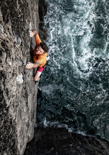 Determined Male Rock Climber Climbing Cliff By Sea