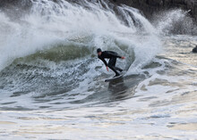 Male Surfer Surfing On Sea At Broad Haven South Beach, Wales, UK