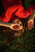Young Woman In Red Dress Holding Cherry Tomatoes While Lying On Grass During Sunny Day