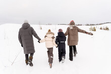 Parents With Children Walking On Snow Covered Landscape Against Sky