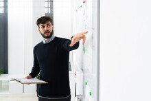 Businessman Having Presentation In Office, Pointing At Whiteboard