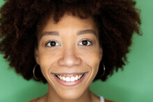 Happy Afro Woman Against Green Wall In New Loft Apartment