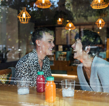 Happy Friends Laughing While Siting By Restaurant Window