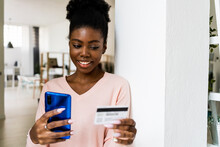 Woman With Credit Card Smiling While Using Mobile Phone At Home